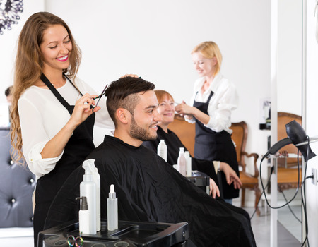 Cheerful young guy cuts hair at the hair salon