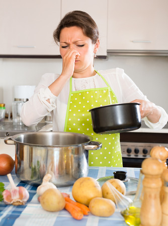 Young housewife pinched her nose avoiding bad smell from pan