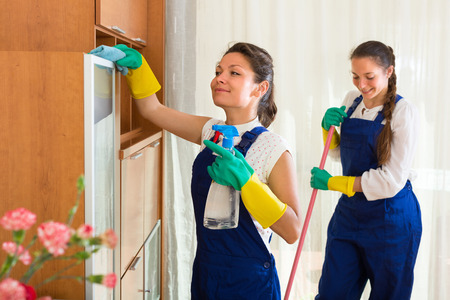 Photo pour Smiling professional cleaners team cleaning in the house with rags and mop. Selective focus - image libre de droit
