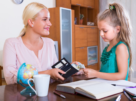 Allowance of pocket money:  little girl and smiling mother with purse