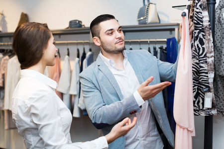 Young store clerk serving purchaser at fashionable apparel store