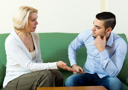 Attractive man and his mature girlfriend having serious conversation indoors