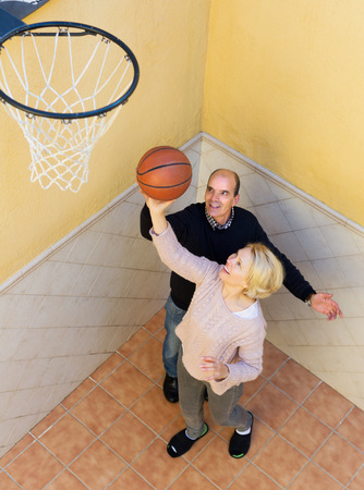 Mature couple throwing the ball into basket