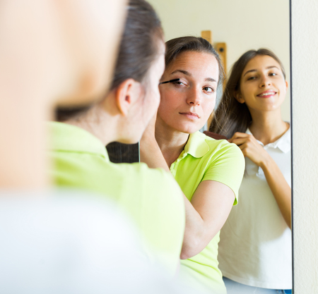Beautiful young girls doing make-up for party in front of the mirror