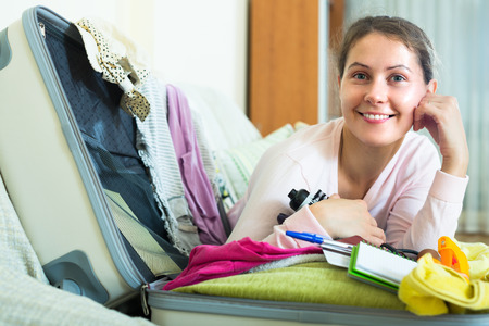 Smiling woman with laptop preparing for travel and dreaming about vacations at home