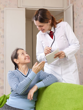 joyful mature woman tells the doctor the symptoms of malaise on couch