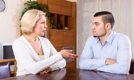 Foto de Sad man and his mature girlfriend having serious conversation indoors - Imagen libre de derechos
