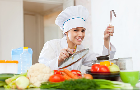 Portrait of happy female cook in white works with ladle