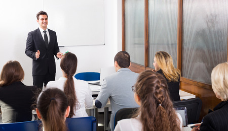 Photo pour Group of attentive adult students with teacher in classroom at business training - image libre de droit