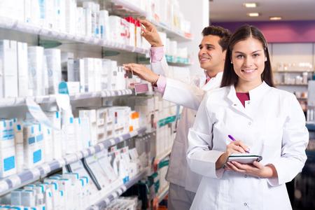 Portrait of two friendly pharmacists working in luxury pharmacy