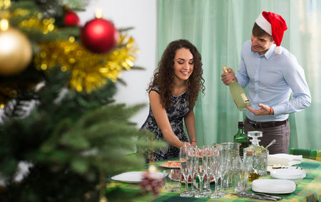 Couple serving New Year table in home