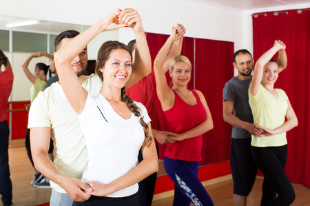 Smiling couples dancing Latino dance in class
