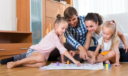 Photo pour Happy young parents and two little daughters playing board game at home - image libre de droit