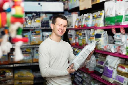 Photo pour Portrait of man watching diet products and smiling in pet store - image libre de droit