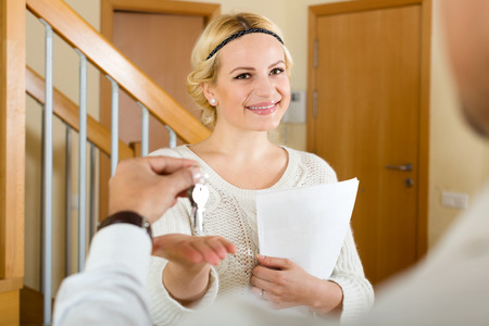 Photo pour Smiling agent giving to man client keys from flat and papers - image libre de droit