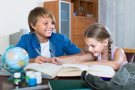Photo pour Portrait of positive spanish children with textbooks and notes in domestic interior - image libre de droit