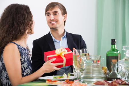 Smiling  man giving present to woman during romantic dinner in home