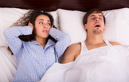 Angry brunette wife disturbed with husband loud snoring