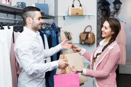 Photo pour Smiling customer with cheerful female shop assistant at boutique. Focus on man - image libre de droit