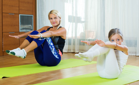 Happy young woman and little girl doing morning exercises indoorsの写真素材