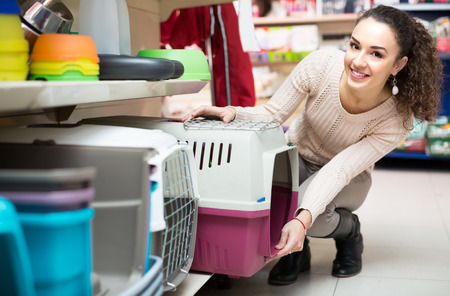 Photo pour Ordinary female customer buying kennel for pet in shop - image libre de droit