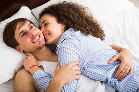 Happy man and woman lying in bed with smile