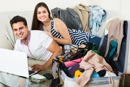 Happy young couple preparing for honeymoon and making planning list