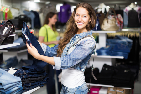 Young smiling woman buying pants in clothing store