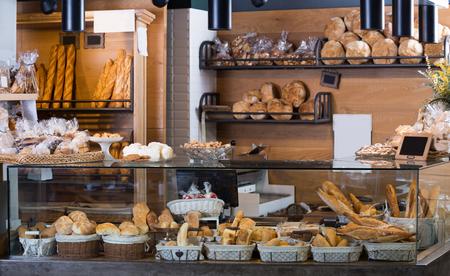 Photo pour Buns, baguettes and other fresh bread at bakery display - image libre de droit