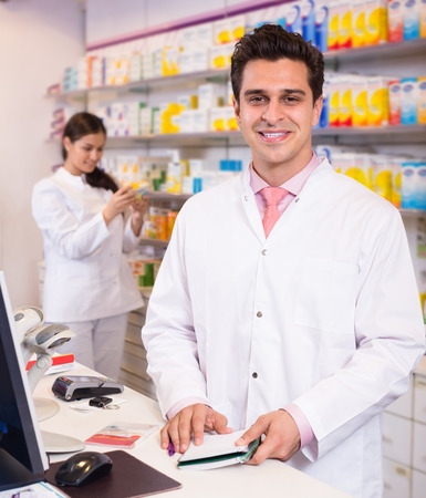 Professional russian pharmaceutists at reception of drugstore ready to help