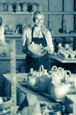 happy female artisan having ceramics in hands and standing in workshop