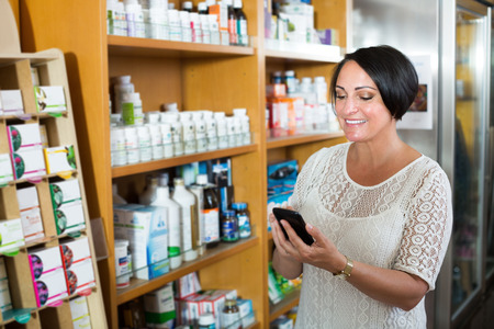 Smiling mature female customer holding mobile phone and choosing goods in healthy food store