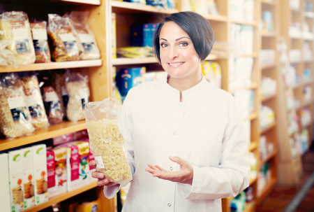 Smiling mature woman seller in uniform holding cereals products in hands near shelfs