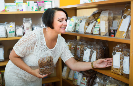 Smiling mature female customer holding with cereal products in healthy food store