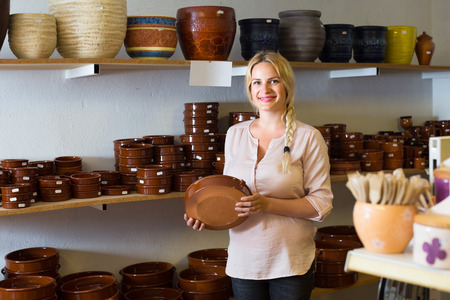female customer choosing ceramics in ceramics workshop