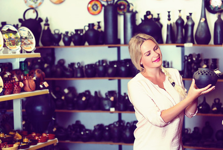 Portrait of blonde woman in craft shop choosing souvenirs