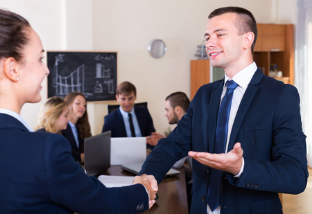 Firm handshake between two young business partners at office meeting