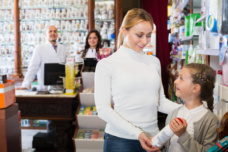 Young mother with a girl consulting two pharmacists at a cash desk in a pharmaceutical store
