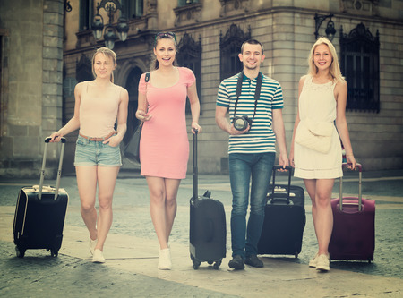 Four positive traveling persons walking together with luggage and looking around in city