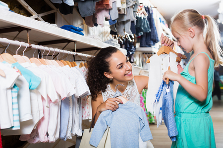 Mother with daughter buying kids clothes in blue color in shop