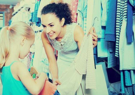 joyful young woman selecting pink dress with her little  daughter  in children clothes store