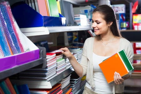 Photo pour ?smiling woman shopping notebooks and writing paper in stationary store - image libre de droit