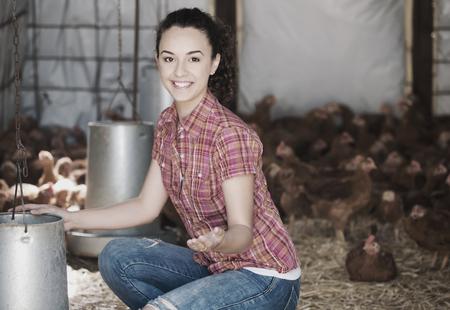 Happy woman farmer giving feeding stuff to chickens in farm house