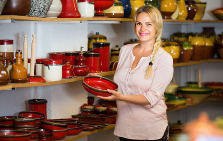 merry female customer picking red glazed crockery in ceramics workshop