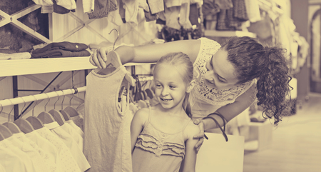 Young cheerful woman with small girl choosing blue clothes in kids apparel boutique