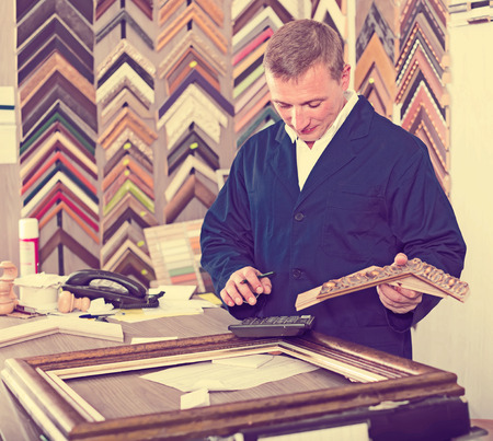 Photo pour male seller standing in picture framing studio with wooden details - image libre de droit