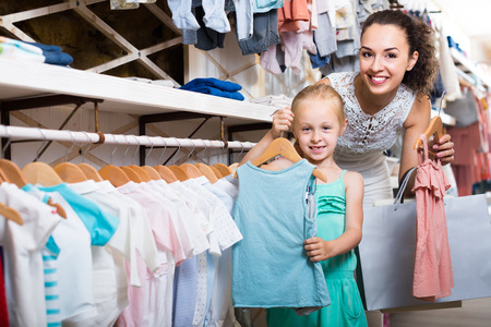 young happy mother with daughter buying kids clothes in shop