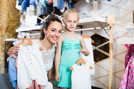 young smiling mother with daughter buying baby pajamas in white color in kids section