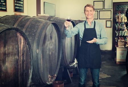 Portrait of male seller in uniform promoting to taste wine before purchasing it in cellar