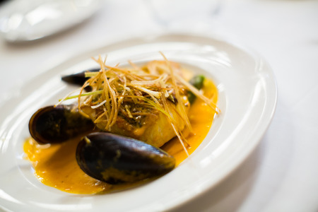 baked white fish with mussels on a plate, close up